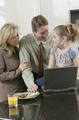 Family and laptop in kitchen