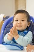 Asian baby clapping in highchair