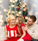 christmas, holidays, family and people concept - happy mother, father and little girl with gift box kissing over living room and christmas tree background