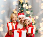 christmas, holidays,  family and people concept - happy mother, father and little girl in santa helper hats with gift boxes over living room and christmas tree background