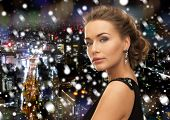 people, holidays, christmas and glamour concept - beautiful woman in evening dress wearing earrings over snowy night background