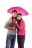 Couple standing underneath an umbrella on white background