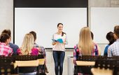 education, high school, teamwork and people concept - smiling student girl with notebook standing in front of students in classroom