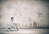 Little joyful cute boy riding tricycle on road