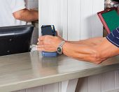 Mid section of senior man paying through smartphone at cash counter