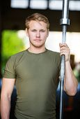 Portrait of confident male athlete holding barbell bar at gym
