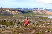 picture of squatting  - Fitness girl exercising outdoors doing jump squat in amazing nature landscape - JPG
