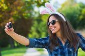 woman taking selfie, wearing bunny ears