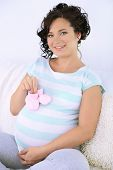 Young pregnant woman sitting on sofa and holding pink baby shoes in room