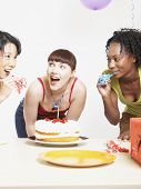 Three women with cake at party