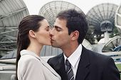 Hispanic couple kissing in front of satellite dishes