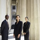 Portrait of businesspeople standing next to columns