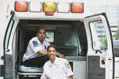African female and male EMTs in ambulance