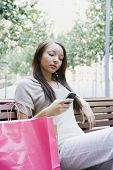 African woman looking at cell phone on park bench