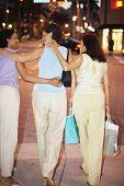 Rear view of Hispanic women walking on sidewalk with shopping bags