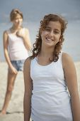 foto of pre-adolescent girl  - Teenage girl smiling on beach with friend in background - JPG