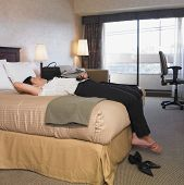 Asian businesswoman laying on hotel bed