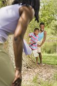 African sister and brother playing with mother in park