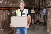 Warehouse worker smiling at camera carrying a box in a large warehouse
