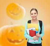 education, holidays, school and people concept - smiling student girl with books and backpack over halloween pumpkins background