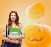 education, holidays, school and people concept - smiling student girl with books and bag over halloween pumpkins background