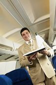 Low angle view of Hispanic male flight attendant carrying wine on a tray