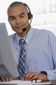 Asian businessman wearing headset at desk