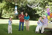 Family watching Hispanic boy hitting pinata at birthday party