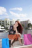 Hispanic woman sitting with shopping bags