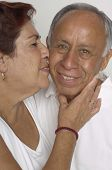 Senior Hispanic woman kissing husband