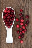 Cranberry fruit in a wooden spoon over oak wood background.