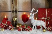 Festively christmas decoration with red gifts and a white reindeer in the snow. Idea for a greeting card or background.