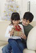 Hispanic brother and sister holding Christmas gift