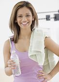 Indian woman holding water bottle and towel