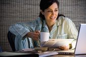 picture of only mature adults  - Hispanic businesswoman working in pajamas - JPG