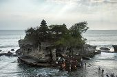 SEPTEMBER 17, 2014, BALI, INDONESIA: Tourists and devotees throng the Tanah Lot Temple. The ancient