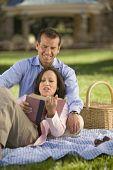 Hispanic couple reading on picnic blanket