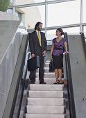 Hispanic businesspeople on escalator