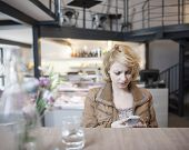 Worried young woman reading text message on cell phone in cafe