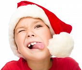 Little girl in santa hat is trying to touch the pompon with her tongue, isolated over white