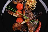 grilled ribs on black plate with vegetables