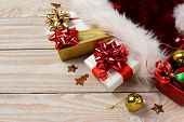 High angle closeup of Christmas presents and Santa Claus hat on a rustic white wood table. Horizontal format with copy space.