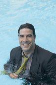 Hispanic businessman in swimming pool