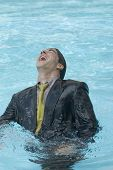 stock photo of adversity humor  - Hispanic businessman in swimming pool - JPG