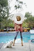 Hispanic woman holding life preserver next to swimming pool