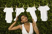 Hispanic woman hanging baby clothing on clothes line
