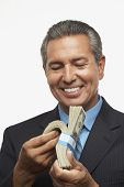 Hispanic businessman holding stack of money
