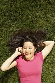 Asian woman talking on cell phone in grass