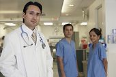 Hispanic male doctor with coworkers in background