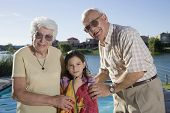 Hispanic grandparents and granddaughter next to swimming pool